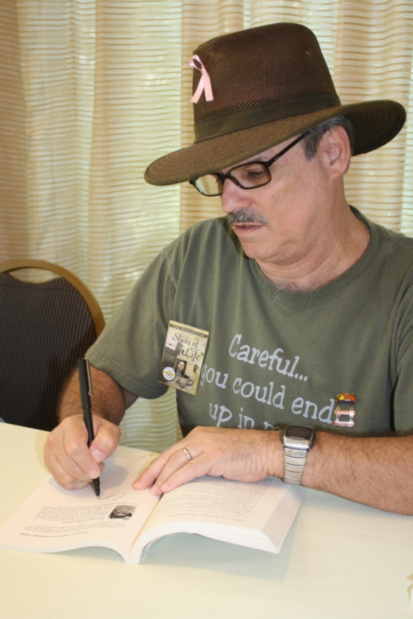 Eugene Orlando several years ago signing his entries in the Florida Writers Association's second anthology.